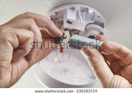 Close Up Of Replacing Battery In Domestic Smoke Alarm - stock photo