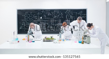 close-up  of researchers in chemistry lab analyzing under microscope on a worktable around lab tools and colorful liquids and a blackboard with formulas on the background - stock photo