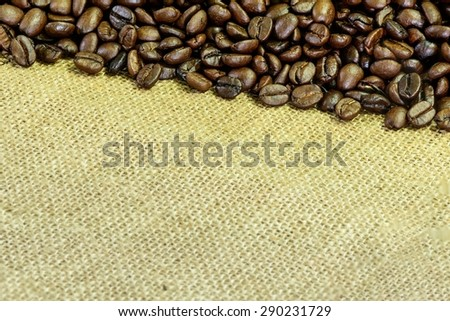 Close up of roasted coffee bean on sack. - stock photo
