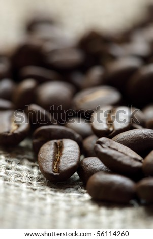 Close up of roasted coffee beans on a burlap sack - stock photo