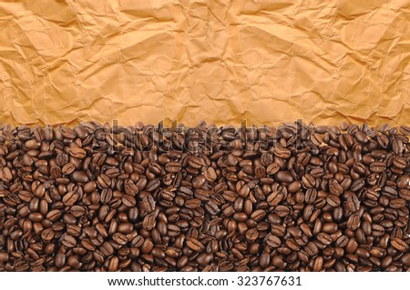 Close-up of roasted coffee beans over old yellow paper - stock photo
