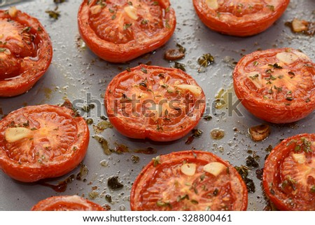 Close-up of roasted tomato halves, hot from the oven with garlic and thyme - stock photo