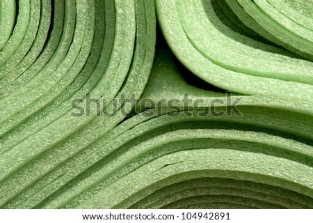 Close up of  rolled up green foam material mats for construction purpose. - stock photo