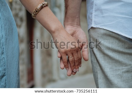Close-up of romantic couple's hands together