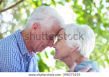 Close-up of romantic senior couple standing face to face - stock photo