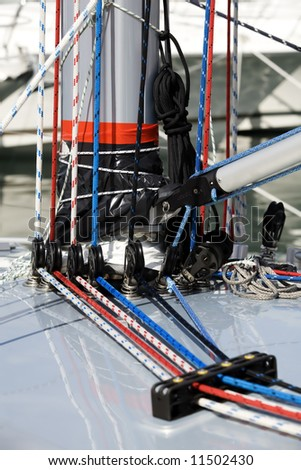 Close up of ropes and equipment on the side of a mast on a new yacht. - stock photo