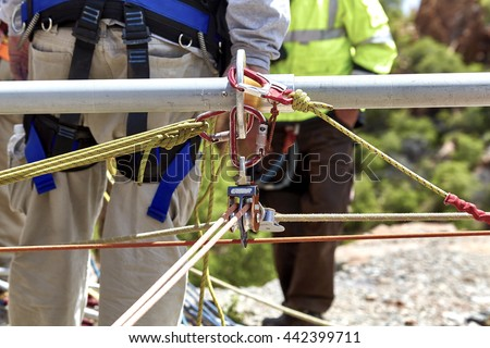 Close up of ropes and pulleys for rescue workers to climb down the side of the cliff. - stock photo
