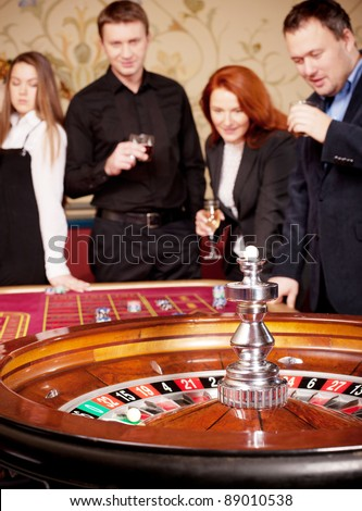 Close up of roulette table in casino with group of people on background - stock photo