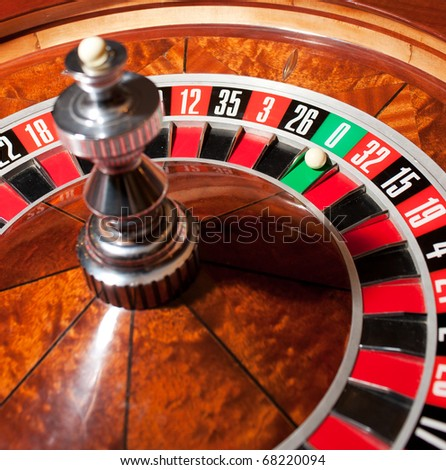 Close up of roulette with while little ball on zero. You're welcome to visit casino and try this game to get satisfaction from life.