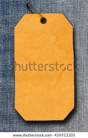 Close up of rumpled brown paper label  with brown pin on destroyed torn blue jeans background   - stock photo