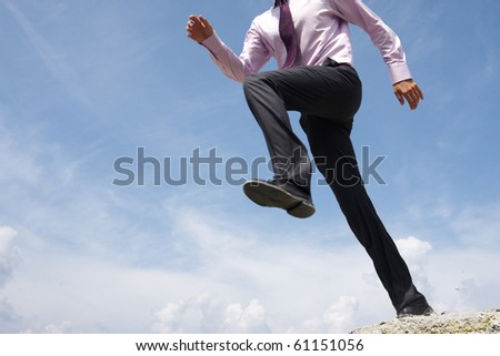 Close-up of running man on background of bright blue sky with white clouds - stock photo