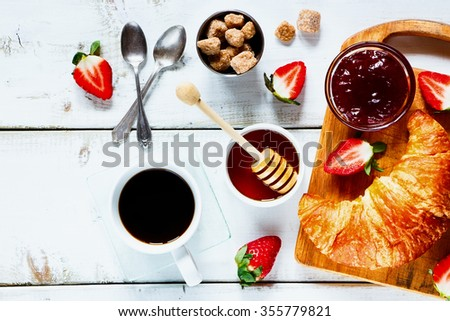 Close up of rural breakfast with fresh croissant, cup of coffee, fruity jam, honey and strawberries on rustic white wooden background. Top view. - stock photo