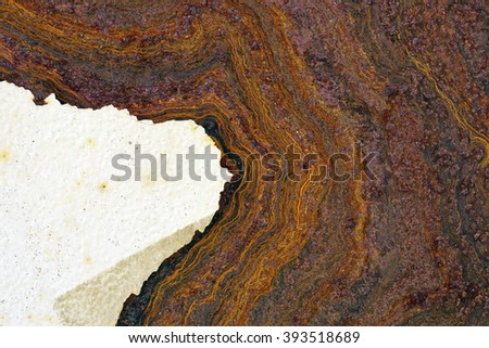 Close up of rusted and corroded  rough steel sheet metal surface with rust stains and part of peeled white paint , abstract grunge textured background - stock photo