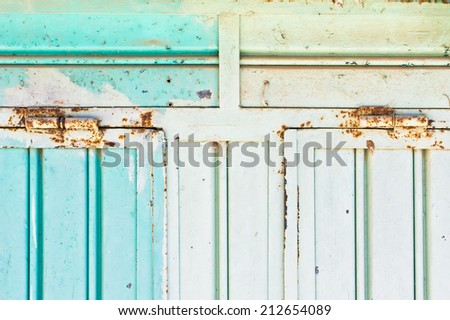 Close up of rusty hinges of a blue metallic shutter - stock photo