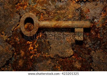 Close up of rusty vintage key lying on old iron plate - stock photo