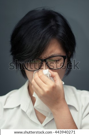 Close up of sad woman with a tissue. Short hair female sneezing. ILLness, depression and allergy concept. Asian girl wear glasses sneezing in a tissue.