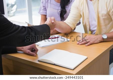Close up of salesman shaking a customer hand at new car showroom - stock photo