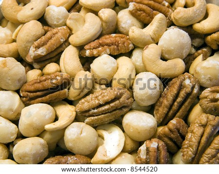 Close up of salted mixed nuts with pecans cashews and macadamias - stock photo