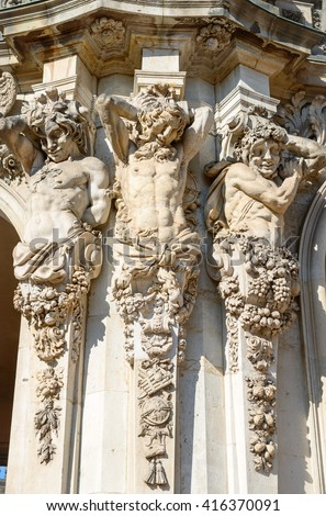 Close-up of sandstone sculptures of satyrs as atlantes on the pilasters of pylon of entrance under Rampart pavilion in Dresden, Saxony, Germany.