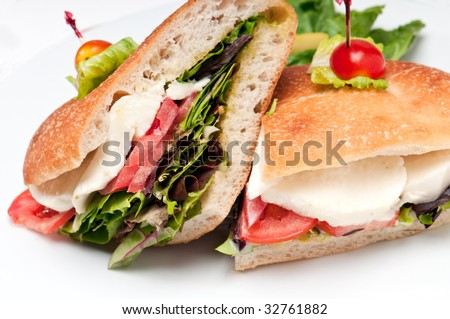 Close up of sandwich of mozzarella, lettuce and tomato. - stock photo