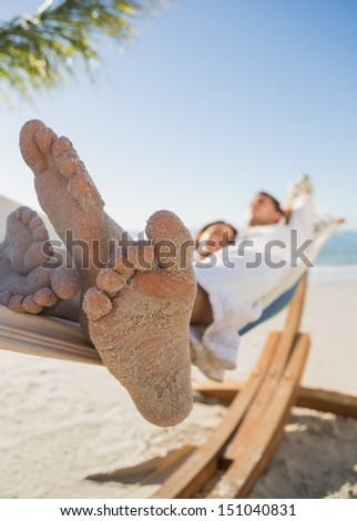 Close up of sandy feet of couple sleeping in a hammock on the beach - stock photo