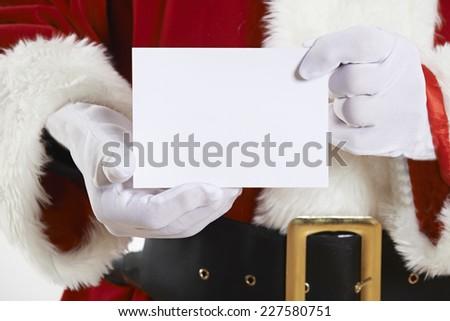 Close Up Of Santa Claus Holding Blank Invitation - stock photo