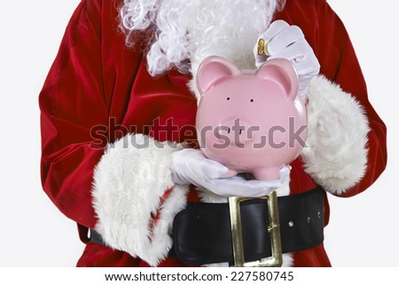 Close Up Of Santa Claus Putting Coin Into Piggy Bank - stock photo