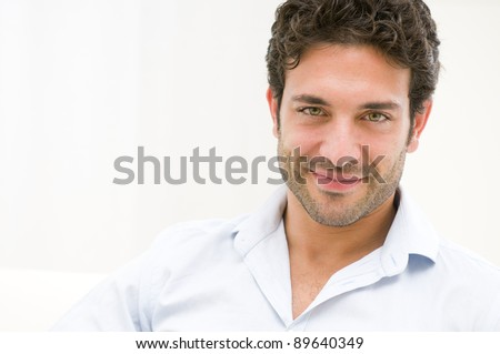 Close up of satisfied smiling guy looking at camera at home - stock photo