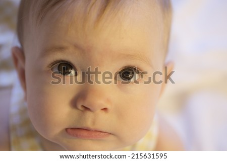 close-up of scared or confused expression on baby face - stock photo