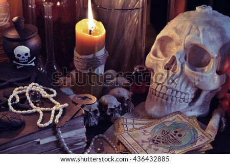 Close up of scary skull, burning candle, old book, jewelry and tarot card The Death.  Halloween or esoteric concept. Black magic and occult vintage objects, divination rite, magic and evil interior