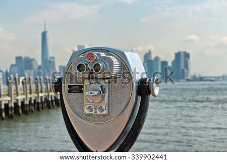 Close Up of Scenic Binoculars with View of New York City Skyline in Background, as seen from Pier of Liberty Island, New York, USA - stock photo
