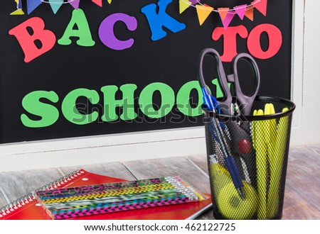 Close up of school supplies with back to school chalkboard in the background.