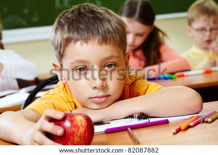 Close-up of schoolboy putting his head on arm and looking at camera - stock photo