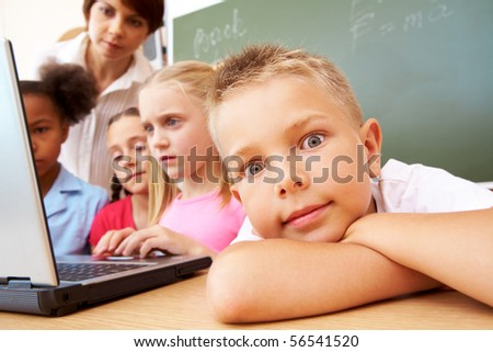 Close-up of schoolboy putting his head on arm during the lesson - stock photo