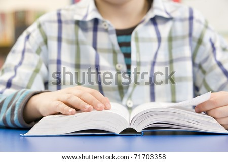 Close Up Of Schoolboy Studying Textbook In Classroom - stock photo