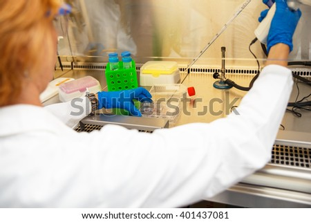 Close up of scientist hand during scientific experiment in laboratory - stock photo