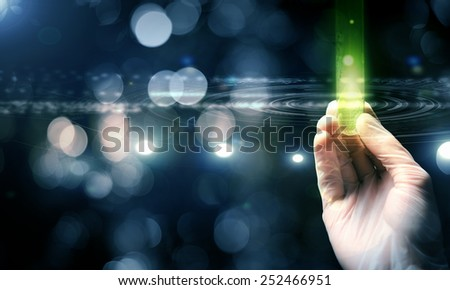 Close up of scientist hand holding tube with leaf - stock photo