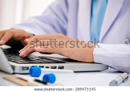 close up of scientist recording chemical tubs onto computer - stock photo