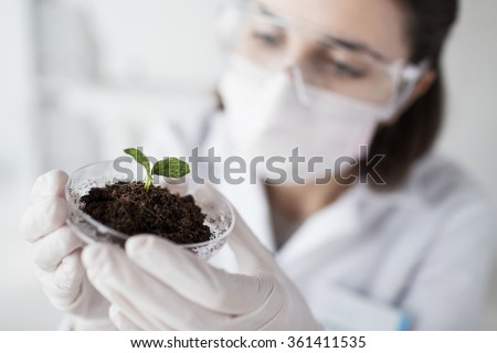 close up of scientist with plant and soil in lab - stock photo