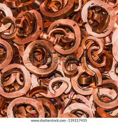 Close up of scrapheap of copper from hole punching and shearing process, waiting for recycling, square cropped - stock photo