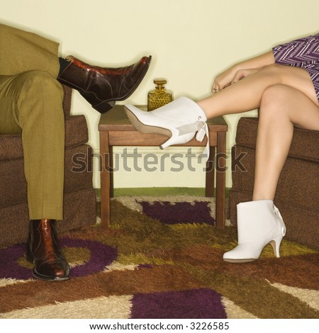 Close-up of seated Caucasian mid-adult male and female legs wearing vintage boots. - stock photo