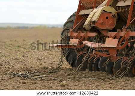 Close-up of seeding machine at field. - stock photo