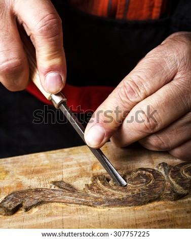 Close Up of senior carpenter restoring old furniture in his workshop - stock photo