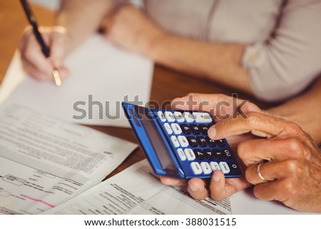 Close up of senior couple counting bills at home - stock photo