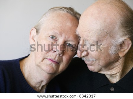 Close-up of senior couple focusing on worried woman - stock photo