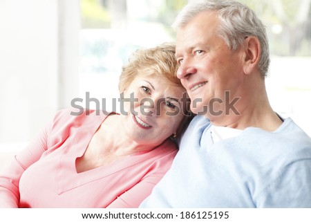Close-up of senior couple sitting in sofa at living room. - stock photo