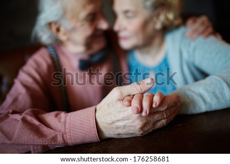 Close-up of senior female held by her husband - stock photo