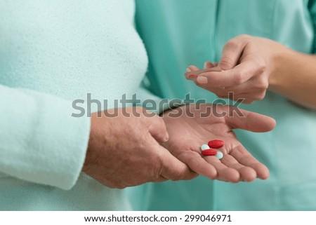 Close up of senior lady in nursing home taking pills - stock photo