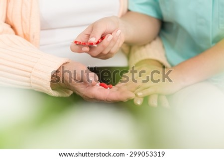 Close up of senior lady in rest home taking medicines - stock photo