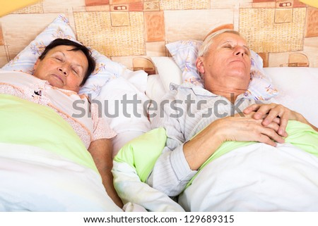 Close up of senior man and woman sleeping in bed. - stock photo